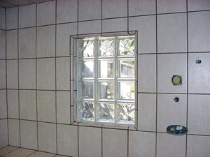 2 rows of 8 x 8 Clear Glass Block with 1 row of 8 x 8 Obscure Glass Block above and 1 row below set in a tile jam made with 10 x 13 flat tile and 1 x 6 quarter round adds light into the shower of this residence in Slidell Louisiana.