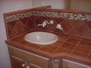 Daltile Cotto Antico Rosso 6 x 6 tile with matching quarter round and sink rail trim along with Casa dalce Fascie Opus multicolor accent listello make up this guest bathroom vanity top.