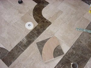 Breccia Paradiso cut from 12 x 12 tile form the radius corners in the border of this foyer.