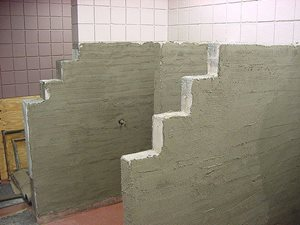 Cement Mortar Scratch Coat over galvenized metal lath mechanicly fastened to painted Concrete block. TCA Method W-221
